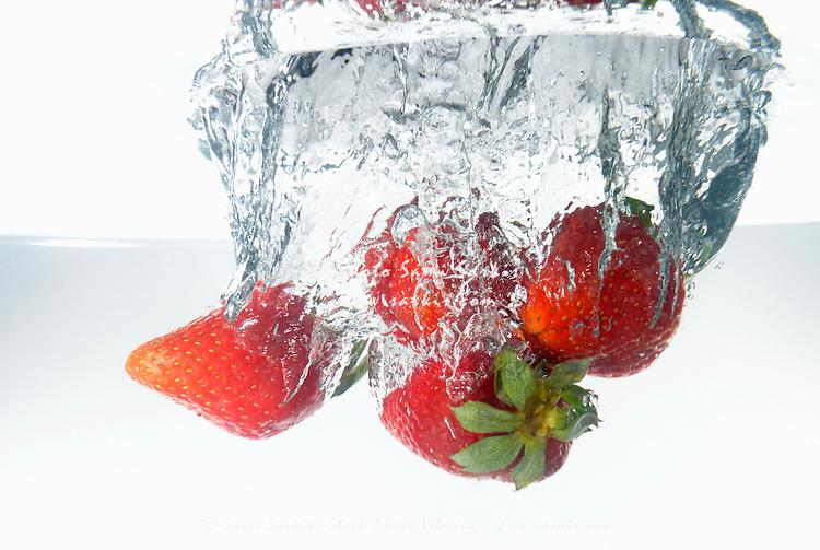 Strawberries fruit splashing underwater, white background, studio