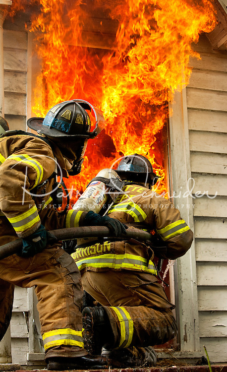 Firefighters with Charlotte Fire Department (CFD) practice their fire fighting skills during a controlled burn of a house. Homeowners sometimes donate vacant structures for burning by the fire department.  In addition to relieving the area of an abandoned building, the controlled burns also serve as training opportunities for fire fighters.