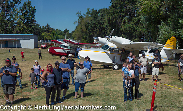 Attendees at the 2019 Clear Lake Seaplane Splash-In, Lakeport, Lake County, California  are watching a seaplane taxi onto the Natural High School lawn.  Two Grumman Widgeons, N3TD, a SCAN Type 30,and N8661, a Grumman G-44A , parked  in the background.