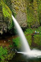 A family enjoys Ponytail Falls, also know as the Upper Horsetail Falls, Columbia River Gorge National Scenic Area, Oregon