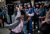 """Seoul, South Korea.May 1, 1987..The Korean middle-class began joining the students in their assault on the government and riot police...After two decades of building an economic miracle, in the summer of 1987 tens of thousands of frustrated South Korean students took to the streets demanding democratic reform. """"People Power"""" Korean-style saw Koreans from all social spectrums join in the protests...With the Olympics to be held in South Korea in 1988, President Chun Doo Hwan decided on no political reforms and to choose the ruling party chairman, Roh Tae Woo, as his heir. The protests multiplied and after 3 weeks Chun conceded releasing oppositionist Kim Dae Jung from his 55th house arrest and shaking hands with opposition leader Kim Young Sam. Days later he endorsed presidential elections and an amnesty for nearly 3,000 political prisoners. It marked the first genuine initiative of democratic reform in South Korea and the people had their victory."""