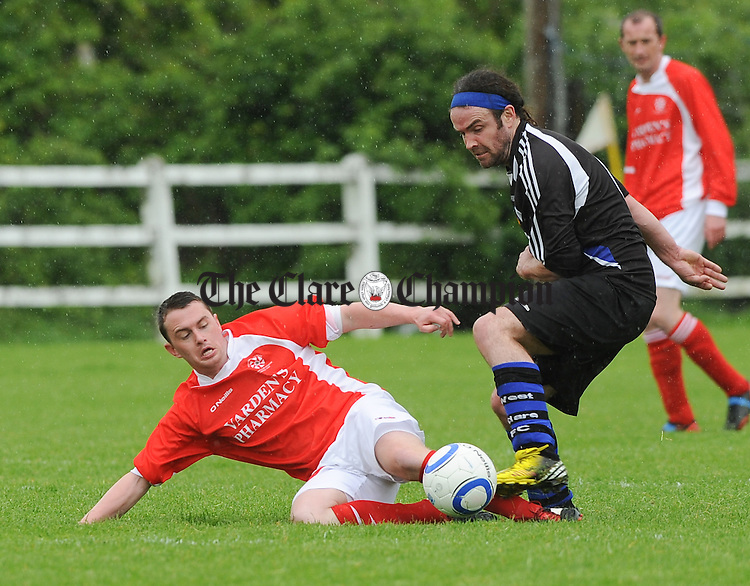 Darren Cullinan of Newmarket Celtic A in action against Brian Harte of West Clare FC during their Cup semi final game at Doora. Photograph by John Kelly.