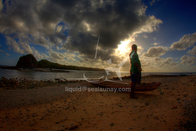 a local man with his canoe on the beach at Boboeina Island in the Louisiade Archipelago..The Louisiade Archipelago is a string of ten larger volcanic islands frequently fringed by coral reefs, and 90 smaller coral islands located 200 km southeast of New Guinea, stretching over more than 160 km and spread over an ocean area of 26,000 km  between the Solomon Sea to the north and the Coral Sea to the south. The aggregate land area of the islands is about 1,790 kmu178  (690 square miles), with Vanatinai (formerly Sudest or Tagula as named by European claimants on Western maps) being the largest..Sideia Island and Basilaki Island lie closest to New Guinea, while Misima, Vanatinai, and Rossel islands lie further east..The archipelago is divided into the Local Level Government (LLG) areas Louisiade Rural (western part, with Misima), and Yaleyamba (western part, with Rossell and Tagula islands. The LLG areas are part of Samarai-Murua District district of Milne Bay. The seat of the Louisiade Rural LLG is Bwagaoia on Misima Island, the population center of the archipelago. .The Louisiade Archipalego is part of the Milne Bay province of Papua New Guinea..It lies between approximately 10 degrees south and 11.5 degrees south, and 151 degrees east and 154 degrees east. It is an area of Islands, reefs and cays some 200 nm long and 50 nm wide, stretching from the south east tip of mainland Papua New Guinea in a east south east direction..