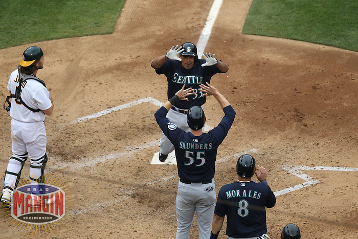 OAKLAND, CA - JUNE 15:  Henry Blanco #33 of the Seattle Mariners celebrates with teammate Michael Saunders #55 after hitting a grand slam against the Oakland Athletics during the game at O.co Coliseum on Saturday June 15, 2013 in Oakland, California. Photo by Brad Mangin