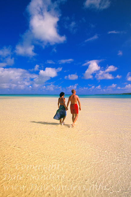 Couple walking down a beautiful beach on an uninhabited island in Aitutaki Lagoon, Cook Islands in the South Pacific.  Model Released