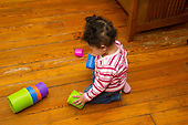MR / Schenectady, NY. Infant (girl, 12 months, African American & Caucasian) plays with round nesting cups. This toy helps her develop coordination, gripping, and cognitive skills. MR: Dal4. ID: AL-HD. © Ellen B. Senisi