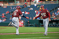 Frisco RoughRiders shortstop Drew Robinson (16) shakes hands with manager Joe Mikulik (25) after hitting a home run during a game against the Springfield Cardinals on June 3, 2015 at Hammons Field in Springfield, Missouri.  Springfield defeated Frisco 7-2.  (Mike Janes/Four Seam Images)