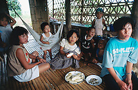 Philippines. Negros Island. Province of Negros Occidental, located in the  Western Visayas region. Barangay (village) Capanuyan. Mothers and children enjoy a meal, seated on the wood floor in their home.  © 1999 Didier Ruef