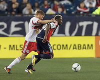 New England Revolution forward Dimitry Imbongo (92) dribbles as New York Red Bulls defender Markus Holgersson (5) pressures too closely. In a Major League Soccer (MLS) match, the New England Revolution (blue) tied New York Red Bulls (white), 1-1, at Gillette Stadium on May 11, 2013.