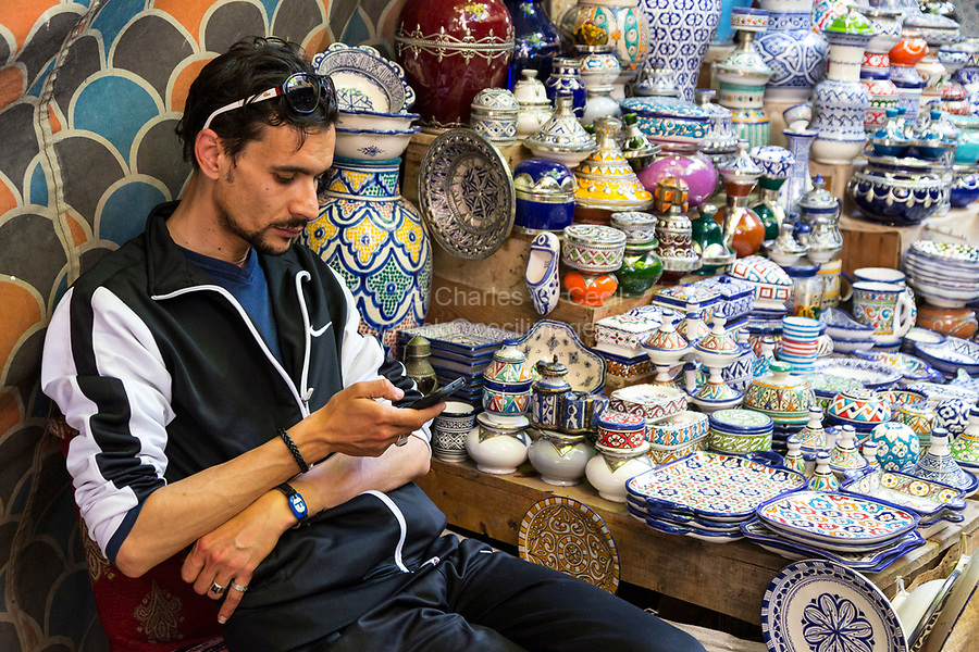 Fes, Morocco.  Ceramics Vendor Checking his Cell Phone, Shops in the Henna Souk, Fes El-Bali.