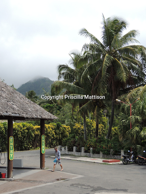 Rarotonga, Cook Islands - September 21, 2012:  A man walks toward a thatch-roofed gas station in a jungle setting.