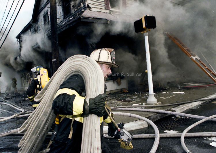 A firefighters carries a hose pas a burning buidling along Rt 71 in Belmar.<br /> 10/10/96