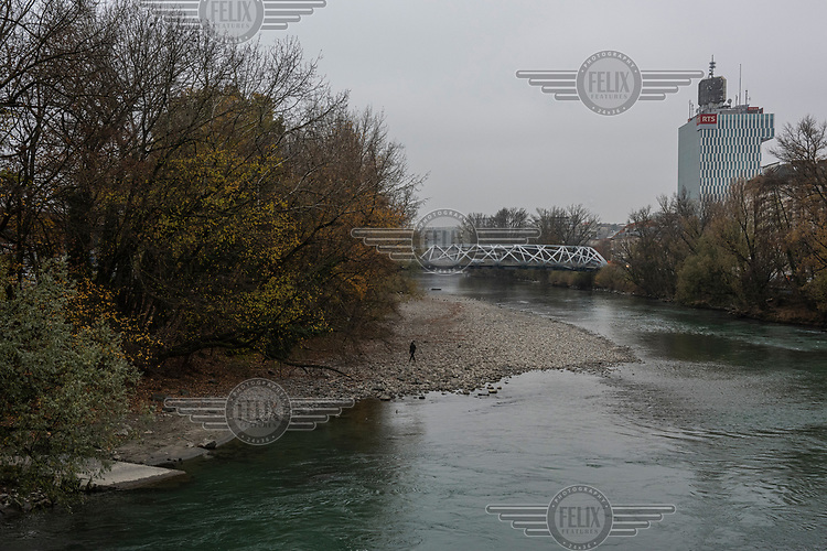 A homeless youth from Morocco, walking beside the Avre River, near where he is sleeping rough. Behind him is the Hans-Wilsdorf Bridge (named after the founder of luxury watchmaker Rolex, and paid for by the foundation that owns the company, head-quartered nearby). On the right is the HQ of the French-speaking branch of the Swiss national television RTS.