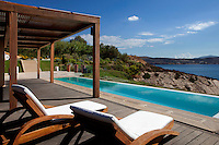 luxury pool area with wooden pergola and deck chairs