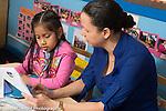 Afterschool homework help program for Headstart graduates Grades K-3 female teacher working with student