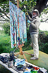 Philip Sutton RA portrait of artist in his garden painting at home in Manorbier Wales UK  1990s