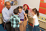 Education Preschool 3 year olds male teacher working with group of children playing with cardboard box