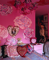 The bright pink feminine bedroom is dominated by large rose motifs painted on the walls and ceiling
