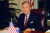 United States President George H.W. Bush poses for photographers after delivering an address to the nation on the budget compromise in the Oval Office of the White House in Washington, D.C. on October 2, 1990. <br /> Credit: Howard L. Sachs / CNP