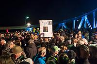 Feierlichkeit zum 30. Jahrestag des Mauerfall am 10. November 2019 an der Glienicker Bruecke. Die Bruecke zwischen Potsdam und Berlin wurde am 10. November 1989 fuer DDR-Buerger geoeffnet.<br /> Im Bild: Eine Teilnehmerin der Feierlichkeit haelt ein Plakat auf dem sie am 10. November 1989 beim Grenzuebertritt zu sehen ist.<br /> 10.11.2019, Berlin<br /> Copyright: Christian-Ditsch.de<br /> [Inhaltsveraendernde Manipulation des Fotos nur nach ausdruecklicher Genehmigung des Fotografen. Vereinbarungen ueber Abtretung von Persoenlichkeitsrechten/Model Release der abgebildeten Person/Personen liegen nicht vor. NO MODEL RELEASE! Nur fuer Redaktionelle Zwecke. Don't publish without copyright Christian-Ditsch.de, Veroeffentlichung nur mit Fotografennennung, sowie gegen Honorar, MwSt. und Beleg. Konto: I N G - D i B a, IBAN DE58500105175400192269, BIC INGDDEFFXXX, Kontakt: post@christian-ditsch.de<br /> Bei der Bearbeitung der Dateiinformationen darf die Urheberkennzeichnung in den EXIF- und  IPTC-Daten nicht entfernt werden, diese sind in digitalen Medien nach §95c UrhG rechtlich geschuetzt. Der Urhebervermerk wird gemaess §13 UrhG verlangt.]