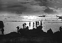 From Coast Guard-manned landing craft, American invaders wade through a golden, shallow surf to hit the beach of Tinian Island.  Units of a mighty task force stand on the horizon - Navy warships, transports and LSTs.  July 1944.  (Coast Guard)<br /> Exact Date Shot Unknown<br /> NARA FILE #:  026-G-2658<br /> WAR & CONFLICT BOOK #:  1170