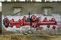 """A calligraphic mural from the Popular Front for the Liberation of Palestine (PFLP) which use draws in the letters is seen in Dir el Balah, Gaza. A masked man and a grenade are seen in the word """"Frontiest"""" or """"people from the Front"""". Photo by Quique Kierszenbaum"""