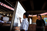 A child writes on the board at the Kartini Emergency School, a free makeshift school under the elevated highway in North Jakarta. Since the early 1990s, twin sisters Sri Rosyati (known as Rossy) and Sri Irianingsih (known as Rian) have used their family inheritance to set up and run 64 schools in different parts of Indonesia, providing primary education combined with practical skills to some of the country's most deprived children.