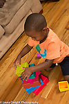 Three year old boy at home building, stacking colorful plastic blocks