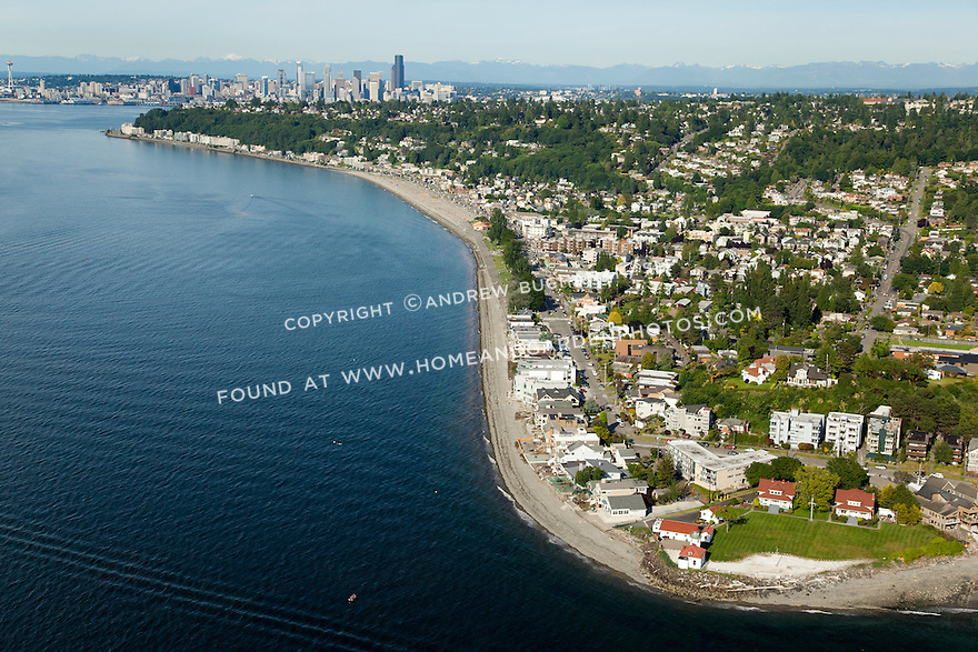 Alki Point Lighthouse and Alki Beach on the West Seattle shoreline of Elliott Bay with downtown Seattle skyline behind; Seattle, WA