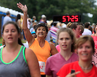 Stacie Gulzinski waves after crossing the finish line during the 32nd annual Charlottesville Women's Four Miler race Saturday in Charlottesville, VA. Photo/The Daily Progress/Andrew Shurtleff
