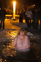 Moscow, Russia, 18/01/2011..A woman crosses herself in the water as Orthodox Christian believers celebrate Epiphany at a lake in eastern Moscow. Priests blessed the waters and followers baptised themselves by total immersion in the freezing lake in temperatures of minus 15C.
