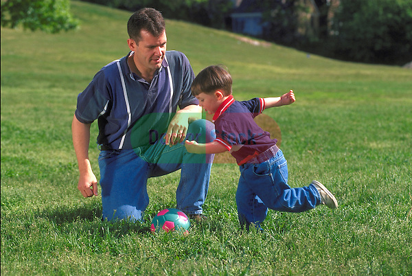 father playing ball with young boy