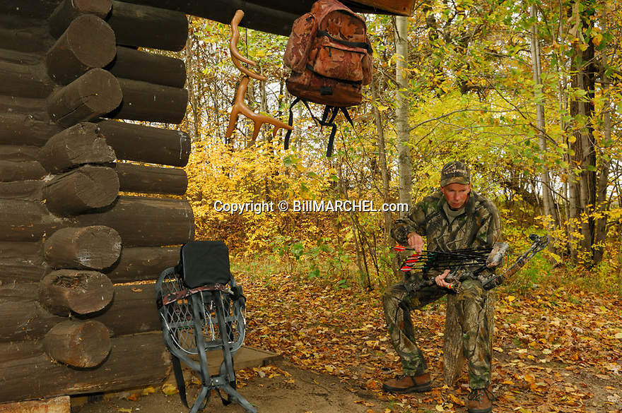 00105-041.16 Bowhunting (DIGITAL) Archer ckecks gear while at hunting shack.  Deer stand, backpack, rattling antlers, Realtree Camo.  H3F1