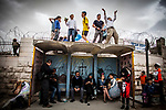 Jewish settler youths dance on a bus station during Purim celebrations in the West Bank city of Hebron Sunday March 12 2017. Purim is a Jewish holiday that commemorates the saving of the Jewish people in ancient Persia , the story is recorded in the Biblical Book of Esther. Photo by Eyal Warshavsky