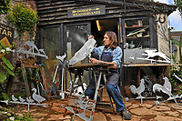 BNPS.co.uk (01202 558833)<br /> Pic: ZacharyCulpin/BNPS<br /> <br /> Pictured: Graham Smith's weather vane's come in all shapes and sizes, he's pictured working on a variety of animal designs<br /> <br /> Something in the wind..<br /> <br /> While Covid caused much of the world to slow down, business has been booming for weathervane maker Graham Smith.<br /> <br /> The former precision engineer has been so busy he has been working seven days a week and has had to close his books to new orders.<br /> <br /> Graham hand-crafts all his weathervanes, creating intricate designs and can even recreate families or significant events.<br /> <br /> With people stuck at home in lockdown and looking at DIY and home improvements, he said he has had his busiest year.