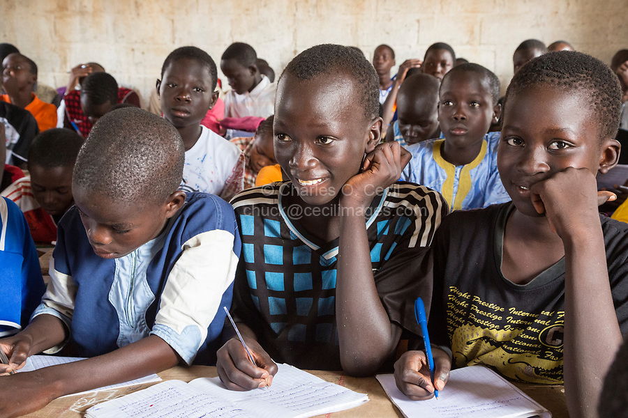 Senegal, Touba.  Senegalese Students at Al-Azhar Madrasa, a School for Islamic Studies, Writing in Arabic in their Notebooks.