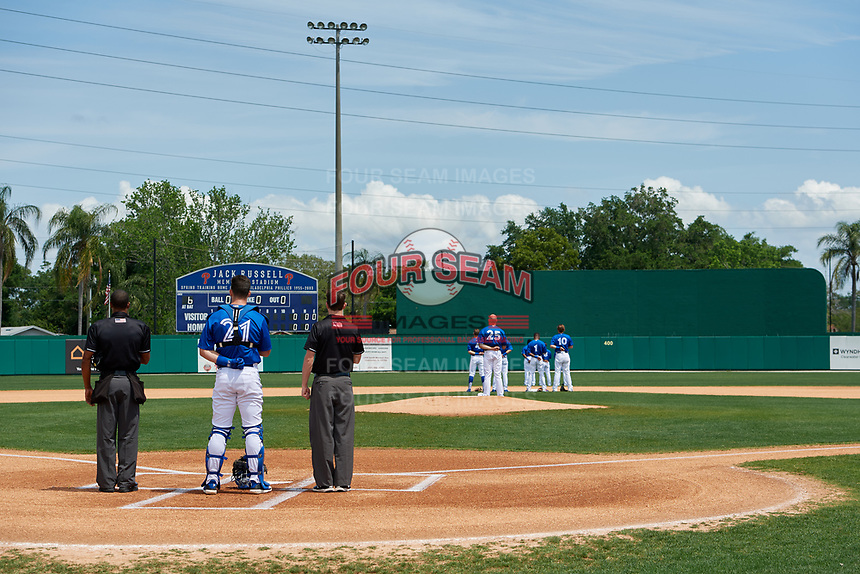 Dunedin Blue Jays catcher Riley Adams (21) stands between umpires Hardie Acosta (left) and Tanner Dobson (right) during the national anthem before a Florida State League game against the Clearwater Threshers on April 7, 2019 at Jack Russell Memorial Stadium in Clearwater, Florida.  Dunedin defeated Clearwater 2-1.  (Mike Janes/Four Seam Images)