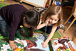 Education Preschool 3-4 year olds two girls working together on floor puzzle using illustration on box as a guide