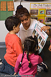 Preschool female teacher working with two children boy and girl looking at planning chart deciding on choice time activities signs in classroom in English and Spanish bilingual education vertical