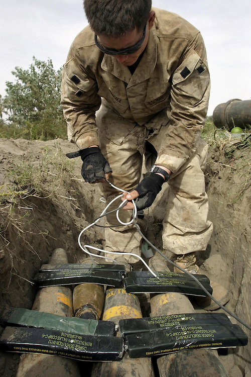 BARWANA, Iraq- Pfc. Michael D. O'Neill, from 1st Combat Engineers Battalion ties a square knot with demolition cord and boosters as he prepares demolition on top of South African 155mm artillery rounds found at a weapon cache. The Marines of Regimental Combat Team 2 conduct counter-insurgency operations with Iraqi Security Forces to isolate and neutralize anti-Iraqi forces, to support the continued development of Iraqi Security Forces, and to support Iraqi reconstruction and democratic elections in order to create a secure environment that enables Iraqi self-reliance and self-governance. (Official USMC photo by Lance Cpl. Shane S. Keller)
