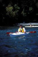Smiling male sea kayaker with ball cap , yellow PFD and red paddle resting,  Cypress Island, San Juan Islands, Washington