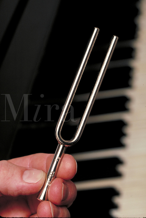 Tuning fork held in front of piano keys.  May not be used in an elementary school dictionary.