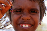 An Aborigine child shows us a honeypot ant.///Un enfant aborigène montre une fourmi pots de miel.