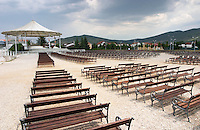 Benches lined up outside in the area that is used for outside sermon service in the summer. Medugorje pilgrimage village, near Mostar. Medjugorje. Federation Bosne i Hercegovine. Bosnia Herzegovina, Europe.
