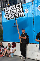 "A protester holds a sign proposing to ""Indict Cheney for 9/11""."