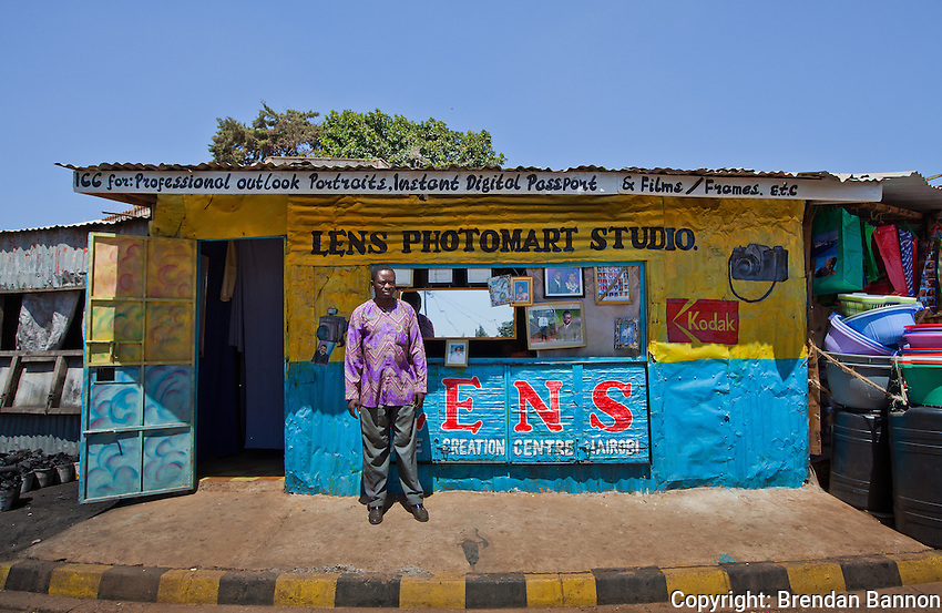 "Lens Photo Studio, Kibera, Nairobi, Kenya.                  Peter Otieno Olendo bought his first camera as a schoolboy in Nairobi. ""My first picture was of  a priest. I was so happy to see that picture. I didn't even mind that I'd cut off half of his head in the frame.""                    After a coup in 1982 made it impossible for him to reach his job as manager of a photo lab he began his own shop serving the residents of Kibera.                          That shop and all of  its contents was burned to the ground in 2008 during the post-election violence.      ""It has been 3 years and ia m slowly building my way back,"" he said.             He shoots passport pictures and portraits from his Kibera studio, often using an old Pentax K1000 camera.               ""When making apicture you have to include the feet. If people can't see their feet they might not pay you. They might say 'I came in here with feet and you've forgotten them. This picture is no good.' """