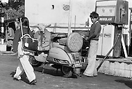 Pakistan - A young boy works at gas station while watching a girl on her way to school - Child labor as seen around the world between 1979 and 1980 – Photographer Jean Pierre Laffont, touched by the suffering of child workers, chronicled their plight in 12 countries over the course of one year.  Laffont was awarded The World Press Award and Madeline Ross Award among many others for his work.