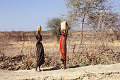 Near Dodoma, Tanzania. Young girls carrying water on their heads in dry arid savannah grassland.