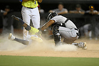 Shortstop Ronny Mauricio (2) of the Columbia Fireflies disappears in a cloud of dirt as he is tagged out trying to steal home by Augusta GreenJackets catcher Andres Angulo (1) on Friday, May 31, 2019, at Segra Park in Columbia, South Carolina. Augusta won, 8-6. (Tom Priddy/Four Seam Images)