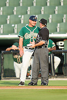 Greensboro Grasshoppers manager David Berg (17) has a chat with home plate umpire Darin Tyson between innings of the South Atlantic League game against the Kannapolis Intimidators at CMC-Northeast Stadium on June 12, 2014 in Kannapolis, North Carolina.  The Grasshoppers defeated the Intimidators 5-2.  (Brian Westerholt/Four Seam Images)